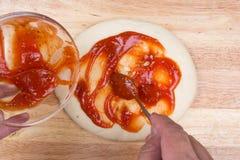 Spreidt saus op pizzakorst uit Stock Foto's