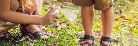 Sprej för mamma- och sonbruksmygga Bespruta krypimpregneringsmedlet på utomhus- BANER för hud, långt format fotografering för bildbyråer