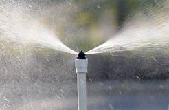sprejande vatten för utloppsrör Arkivfoto