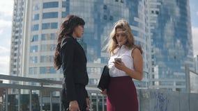 Sprekende bedrijfsvrouwen op de achtergrond van een modern gebouw twee jonge aantrekkelijke vrouwen in formele kostuums stock videobeelden