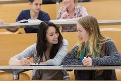 Sprekende studenten in een lezingszaal stock fotografie