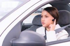 Sprekende telefoon in een auto die een hoofdtelefoon met behulp van stock foto