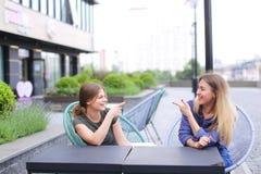 Sprekende vrouwelijke personen die bij straatkoffie in openlucht zitten Royalty-vrije Stock Fotografie