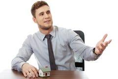 Sprekende zakenman met huismodel door een bureau Stock Fotografie