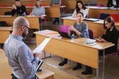 Spreker en multinationale groep studenten in een auditorium royalty-vrije stock afbeelding