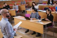 Spreker en multinationale groep studenten in een auditorium stock fotografie