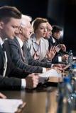 Sprekers die aan persconferentie deelnemen stock foto's