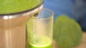 Spremiagrumi che producono il succo di verdura verde dei broccoli Fine su di Juicing a macchina e vetro verde del succo che otten archivi video