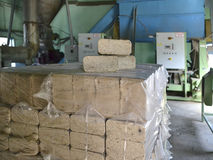 Spreovannye sawdust briquette. Compressed sawdust briquettes for heating in the package in the premises of the production plant Stock Image