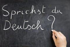 Sprichst du Deutsch Hand Writing Blackboard. Sprichst du Deutsch question handwritten on dirty chalkboard by male hand holding white chalk. Please visit my Royalty Free Stock Image
