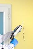 Spricka för påfyllningar för silikontätningsmedelvapen på väggen royaltyfri foto