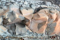 Sprickor och färgrika lager av sandstenbakgrund En stor hög av sandstenar, lagringsutrymme av olik naturlig sandsten Patten Arkivfoton