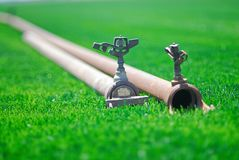 Spridare som fästas till bevattning, leda i rör att lägga på grönt gräs arkivfoton
