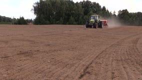 Spridd gödningsmedel för traktor på kultiverat fält i sommar arkivfilmer