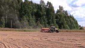 Spridd gödningsmedel för traktor på kultiverat fält nära skog arkivfilmer