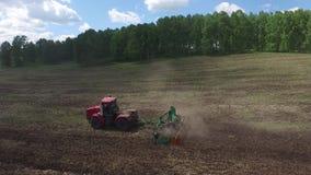 Spridd gödningsmedel för traktor på kultiverat fält nära skog i sommar lager videofilmer