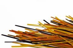 Spridd kulör rå spagetti som isoleras på vit Matbackgrou Fotografering för Bildbyråer