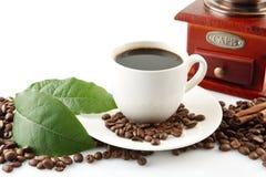 Spridda kaffebönor med koppar kaffe och bladet Royaltyfri Bild