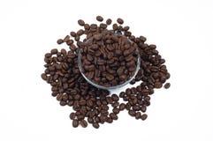 Spridda kaffebönor runt om och inom den glass tillbringaren Fotografering för Bildbyråer