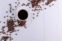Spridda kaffekorn, en kopp och svart choklad p? en vit tr?tabell kopiera avst?nd arkivfoto