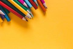 Spridda kulöra blyertspennor på gulingpappersbakgrund kopiera avstånd royaltyfri foto