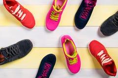 Spridda sportskor på ettfärgat golv, bakgrund Royaltyfria Foton