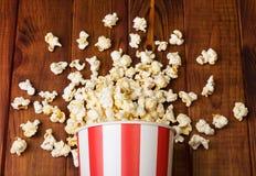 Spridda stycken av den randiga popcornasken på bakgrunden stiger ombord arkivfoto