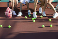 Spridda tennisbollar på domstolen av fot av folk Royaltyfri Bild