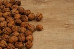 Spridda valnötter på trägolvet Arkivfoton