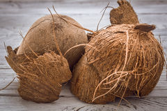 Spridde hela muttrar för kokosnöt shavings av på träbakgrund Arkivfoton