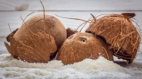 Spridde hela muttrar för kokosnöt shavings av på träbakgrund Royaltyfri Fotografi