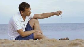 Spridningsand för ung man till och med dina fingrar på stranden stock video