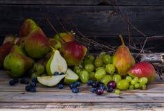 Sprig виноградин и очень вкусной груши на деревянной предпосылке Стоковые Изображения RF