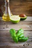 Sprig basil w avocado, wapnie i oliwa z oliwek tła, Fotografia Stock