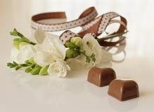 Sprig of freesia flower and chocolates Stock Photo