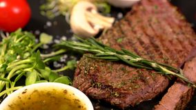 Sprig of fresh rosemary garnish added to steak. Sprig of fresh rosemary garnish being added to a portion of grilled lean beef steak on a black platter with salad stock video