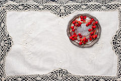 Sprig of red berries  on the  old vintage  lace napkin. Red berries on the old metal plate on the vintage lace napkin on the black wooden table horizontal Royalty Free Stock Images
