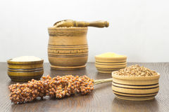 Sprig of sorghum, buckwheat in the box, millet, wooden container. And spoon on the table royalty free stock image