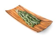 Sprigs розмаринового масла на деревянной плите Стоковая Фотография