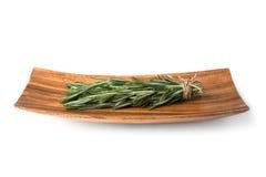 Sprigs розмаринового масла на деревянной плите Стоковое Изображение