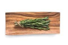 Sprigs розмаринового масла на деревянной плите Стоковые Изображения