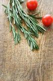 Sprigs томатов розмаринового масла и вишни на верхней части деревянной доски соперничают Стоковая Фотография