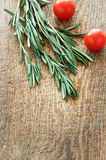 Sprigs of rosemary and cherry tomatoes on a wooden board top vie Stock Photography