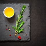 Sprigs of rosemary and olive oil on a cutting board. Top view Stock Images