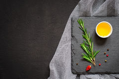 Sprigs of rosemary and olive oil on a cutting board. Top view with copy space Royalty Free Stock Photo