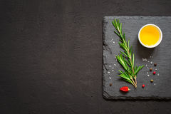 Sprigs of rosemary and olive oil on a cutting board. Top view wi. Th copy space Royalty Free Stock Photos