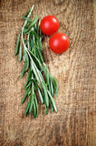 Sprigs of rosemary and two cherry tomatoes on a wooden board top Stock Photos