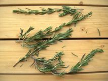 Sprigs of rosemary on the wooden background. Sprigs of rosemary on a rustic table, prepared for cooking, spicy, fragrant herbs, healthy natural food, closeup Stock Photography