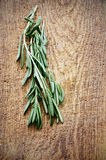 Sprigs of rosemary on a wooden board top view vertical Royalty Free Stock Photo