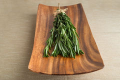 Sprigs of rosemary. On a wooden plate Stock Photo